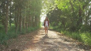 heureux jeune voyageur femme asiatique avec sac à dos marchant dans la forêt.