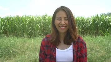 Cheerful asian female farmer and entrepreneur posing in the corn crop and smiling at camera.