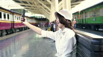 Happy Asian woman passenger with casual taking selfie by smart mobile phone in train station rails for travel in Bangkok city, Thailand.