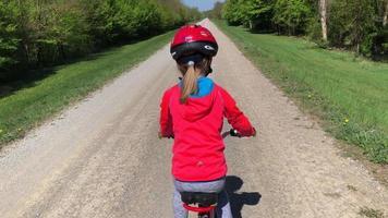 cámara sigue a una niña en bicicleta en 4k