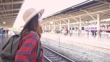 Slow motion - Happy Asian woman waiting the train at train station for travel in summer.