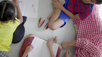 madre asiática jugando con niños en el piso de la sala.