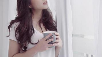 feliz linda mulher asiática sorrindo e bebendo uma xícara de café ou chá perto da janela no quarto.