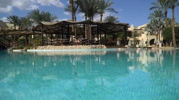 Sunny Hotel Resort with luxury blue swimming pool, Waterslides, palm trees, Beach Umbrellas and sunbeds in Egypt. Rich vacation on the sunny resort. Empty Egyptian hotel with swimming pool video