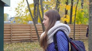 Beautiful young woman wears knitted scarf and walking in autumn park