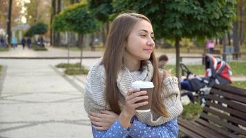 close-up do rosto de uma mulher que bebe chá quente ou café no outono park, ela usa cachecol de malha. menina bebe café de bom humor na caneca video
