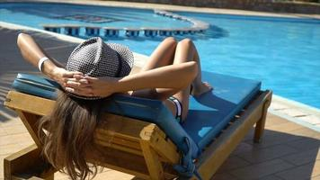 Mulher bonita relaxando em uma espreguiçadeira perto da piscina video