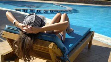 Pretty Woman relajándose en una tumbona cerca de la piscina