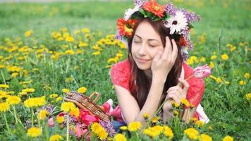 Beautiful woman with wreath picks flowers on meadow. Happy woman in spring or summer season. I love to work with plants video