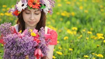 Woman with wreath on head picks lilac and tulip flowers in garden. Happy woman gardener with flowers. Spring and summer. I love to work with plants video