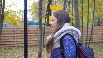 Beautiful young woman wears knitted scarf and walking in autumn park. 4k video motion