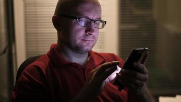 El hombre se para cerca de la ventana en la habitación del hotel y usa un teléfono inteligente.