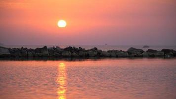 Nascer do sol do fundo vermelho cênico do nascer do sol de 4 k. close-up vídeo do sol nascendo atrás do mar