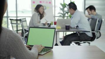 mulher com as mãos digitando o computador portátil com tela verde na mesa no escritório.