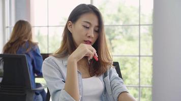 atractiva mujer creativa asiática sosteniendo una taza de café mientras trabajaba en el lugar de trabajo.