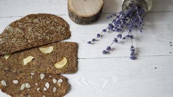pão com linhaça e amêndoas em um fundo branco de madeira.