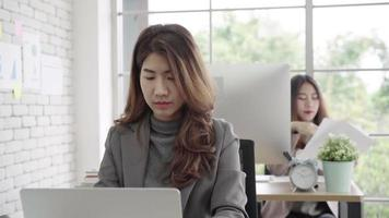Attractive smart Asian business woman in smart casual wear working on laptop. video