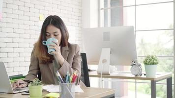 duas jovens empresárias asiáticas trabalhando juntas no escritório. video