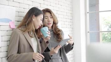 dos jóvenes estudiantes universitarios de negocios asiáticos o compañeros de trabajo tomando café y hablando en la oficina.