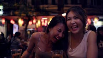 Young Asian traveling women backpacker drinking beer with friends and flirst with man in urban street night party.