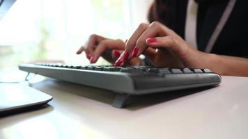 Mulher com as mãos digitando no teclado video