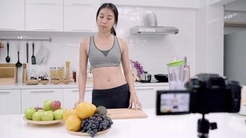 Blogger sporty Asian woman using camera recording how to make orange juice video for her subscriber.