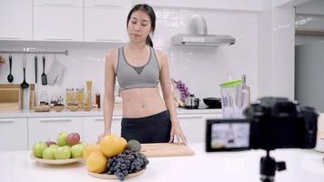 Blogger mujer asiática deportiva que usa la cámara grabando cómo hacer un video de jugo de naranja para su suscriptor.