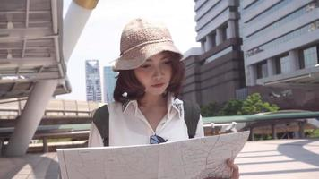 Slow motion - Cheerful beautiful young Asian backpacker woman direction and looking on location map.