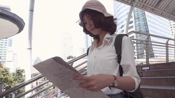 Asian backpacker woman direction and looking on location map while traveling at Bangkok, Thailand.