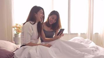 lesbian happy couple sitting on bed hug and using phone together bedroom at home. video