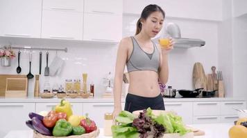 Young Asian woman making salad healthy food while using tablet for looking recipe and drinking orange juice in kitchen. video
