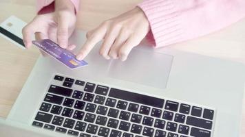 belle femme asiatique utilisant un ordinateur ou un ordinateur portable, acheter des achats en ligne par carte de crédit.
