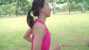 Slow motion - Healthy beautiful young Asian runner woman in park. video