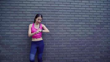 mujer atleta configurando y controlando el progreso mirando el monitor de frecuencia cardíaca en el reloj inteligente. video