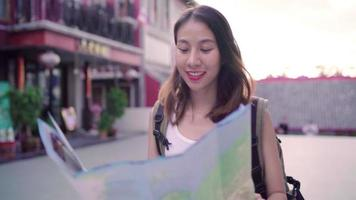 Cheerful beautiful young Asian backpacker woman direction and looking on location map.