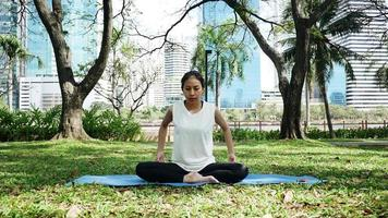 Young asian woman yoga outdoors keep calm and meditates while practicing yoga.