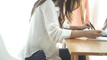 hermosa joven sonriente mujer asiática trabajando en la computadora portátil mientras está sentado en una sala de estar en casa.