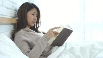 Lifestyle happy young Asian woman enjoying lying on the bed reading book pleasure in casual clothing at home.