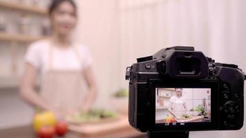Blogger mujer asiática con cámara grabando cómo hacer un video de ensalada de comida saludable para su suscriptor.