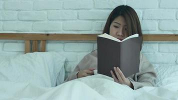 Beautiful asian woman enjoying drinking warm coffee and reading book on bed in her bedroom. video