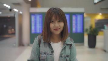 câmera lenta - feliz mulher asiática, sorrindo para a câmera enquanto fica no terminal do aeroporto internacional.
