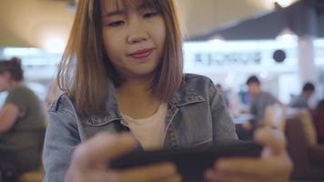 glückliche asiatische Frau, die ihr Smartphone benutzt und überprüft, während sie auf Stuhl in der Terminalhalle sitzt.