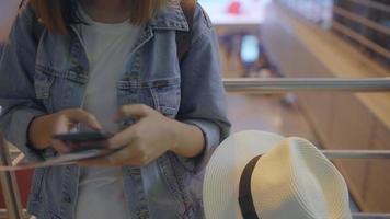 heureuse femme asiatique utilisant et vérifiant son smartphone dans le hall terminal. video