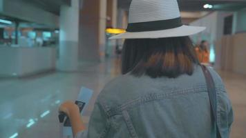 Slow motion - Happy Asian woman using trolley or cart with many luggage walking in terminal hall.