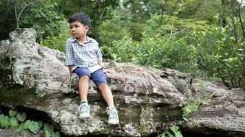 de jongen zittend op een rots in de natuur.