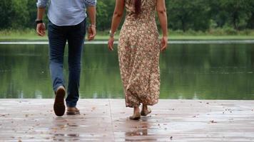 casal sentado no lago sentado na beira de um cais de madeira.