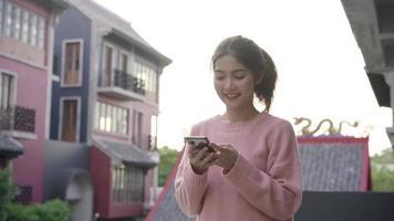 Zeitlupe - asiatische Touristenbloggerin, die Smartphone für Richtung und Blick auf Standortkarte verwendet.