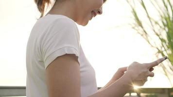 Mujer alegre blogger turista asiático con smartphone para dirección y mirando en el mapa de ubicación.