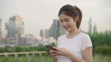 cámara lenta - mujer blogger alegre turista asiático con smartphone para dirección y mirando en el mapa de ubicación.