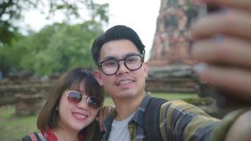 Traveler Asian couple using smartphone taking selfie while spending holiday trip at Ayutthaya, Thailand.